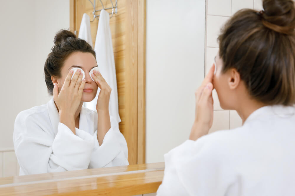 Woman removing makeup from eyes