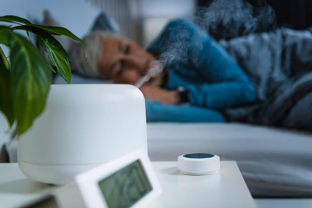 Woman sleeping next to humidifier