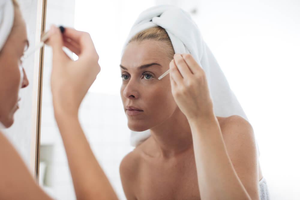 Woman applying face serum