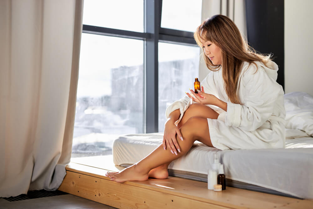 Woman applying skin product to legs