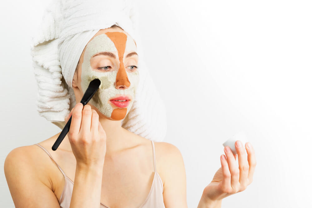 Woman applying multiple face masks