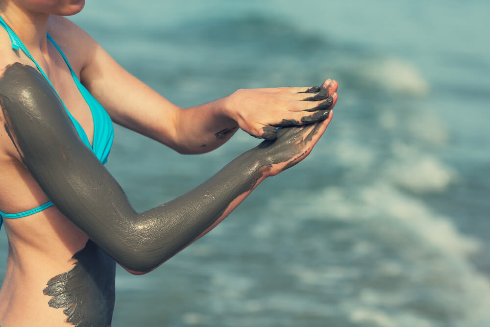 Woman applying sea mud to body