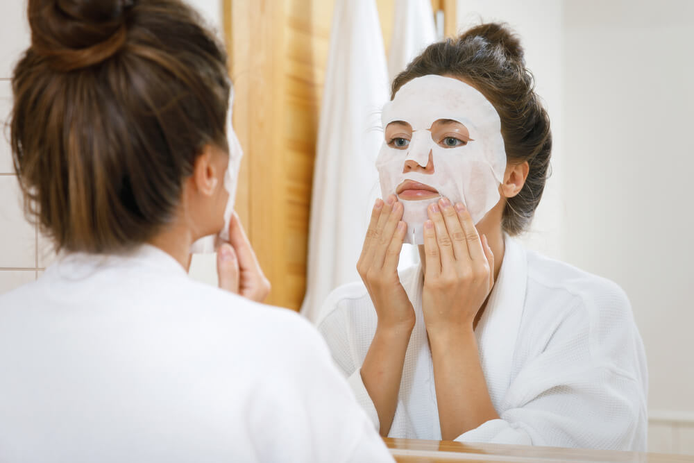 Woman applying sheet mask