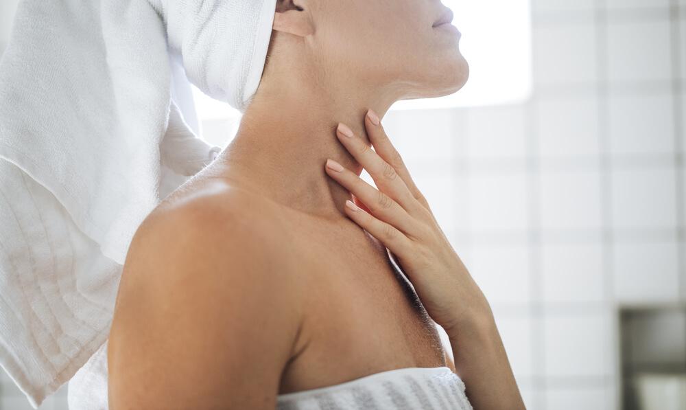 Woman applying neck serum