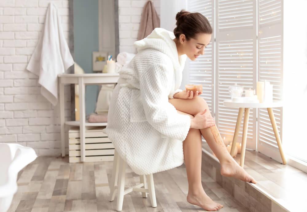 Woman applying body scrub to leg