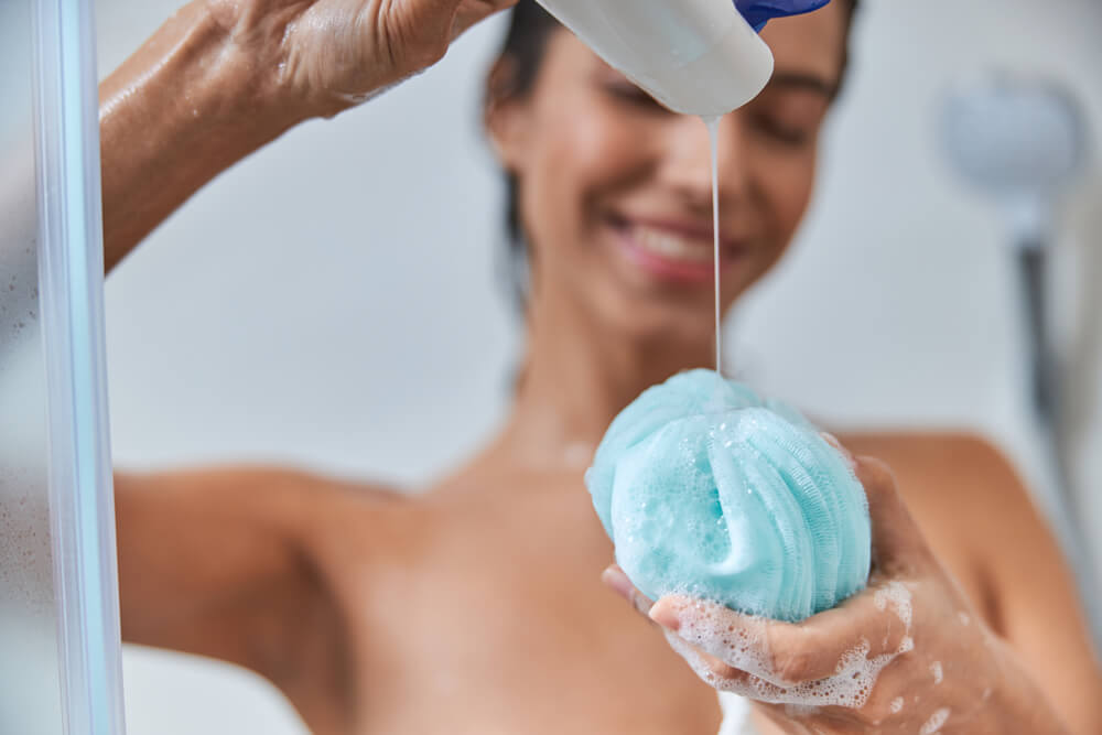 Woman in shower using loofah